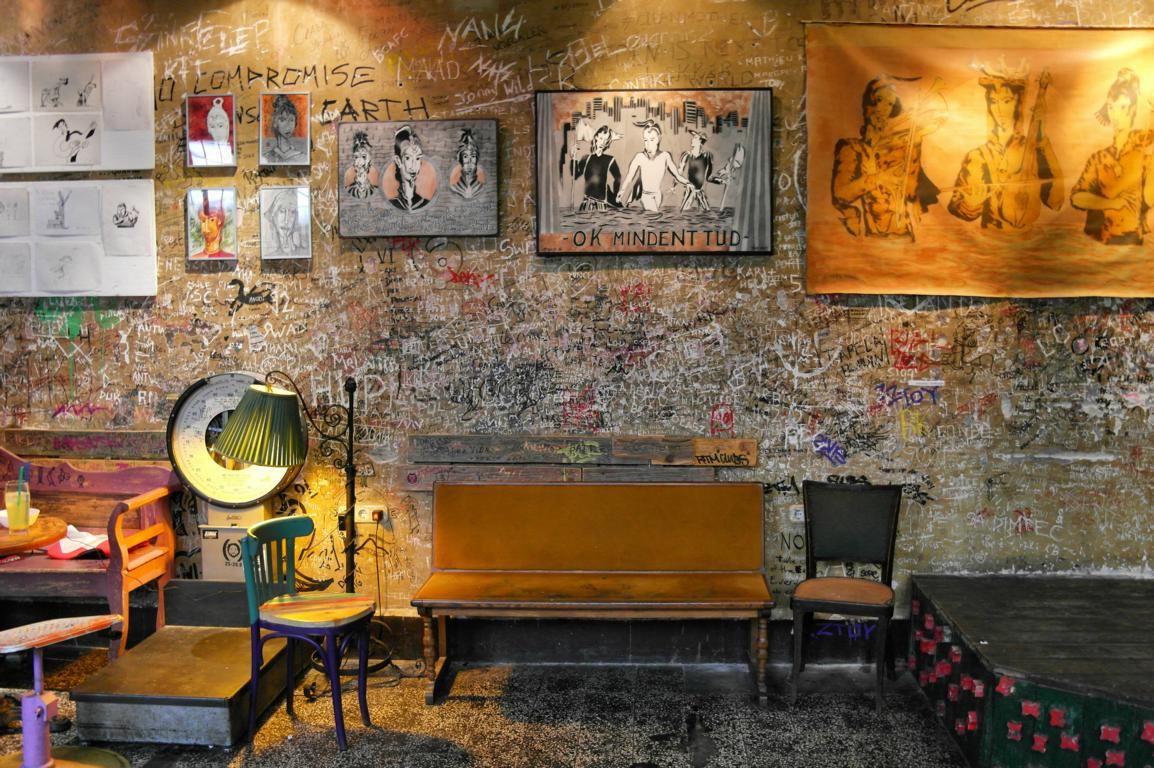 Pictures, chairs and a bench at Szimpla Kert Ruin Bar